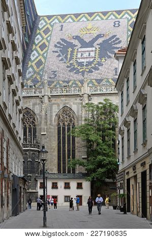 Vienna, Austria - July 12, 2015: Tourists Around St. Stephen Cathedral With Big Coat Of Arms At Roof