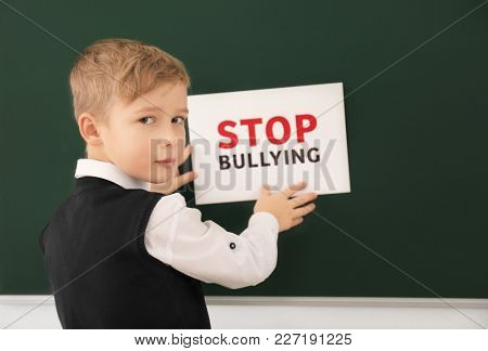 Little boy sticking sign with words