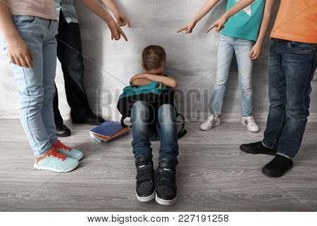 Children bullying little boy with backpack indoors
