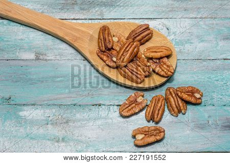 Tasty Pecan  In Wooden Spoon On The Old Background.