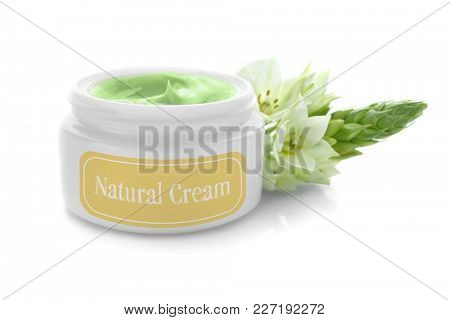 Jar with natural body cream and flower on white background
