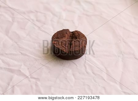 Round Disc Of Traditional Chinese Puer Tea On Crumpled Packaging Paper Background.