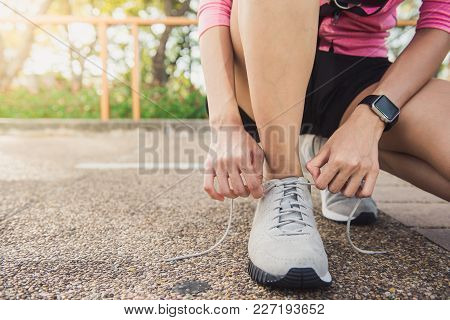 Close Up Of Young Woman Lace Up Her Shoe Ready To Workout On Exercising In The Park With Warm Light