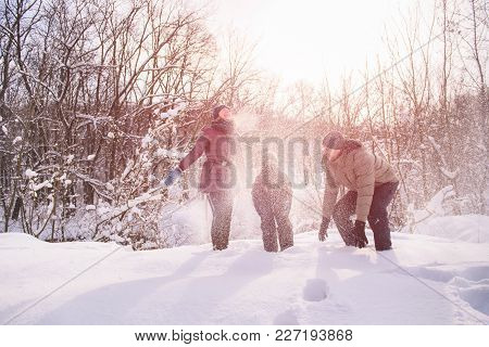 Mother, Son And Father Smiling In Backlight With Snowflakes