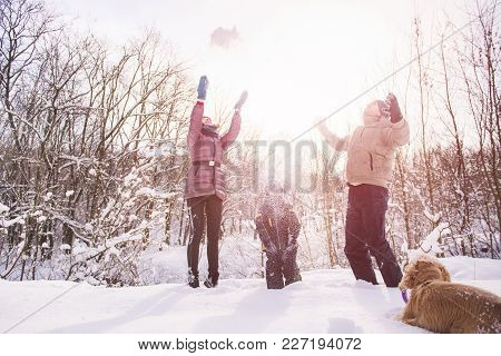 Mother, Son, Father And Dog Smiling In Backlight With Snowflakes