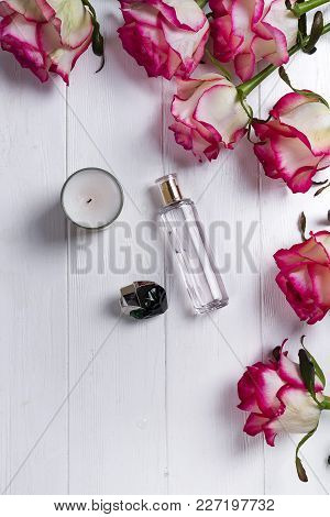 Perfume Bottle, Candle And Pink Rose On White Wooden Background, Flat Lay