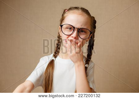 Little Emotional Girl With Glasses In A White T-shirt