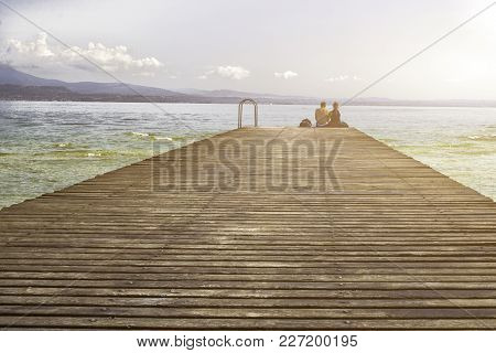 The Couple Sitting On The Pier Dangling Legs Observed Sunset Over The Lake.