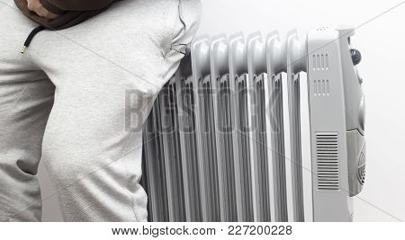 Unknown Man Sitting And Relaxing On Oil Heater