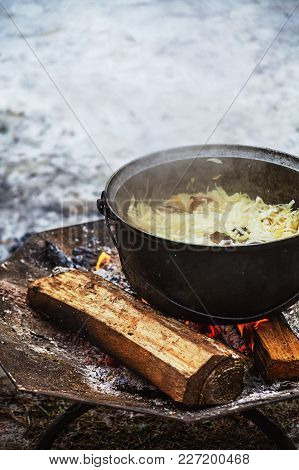 Cabbage With Meat Cooking In A Cauldron On Open Fire During A Festival In Winter.