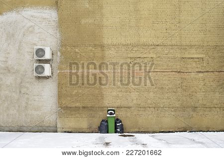 .green Recycle Bin Near The Large Brick Wall And Air Conditioner Compressor Unit On Wall