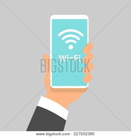 Free Wifi Sign Concept. Hand Holding Mobile Phone With Free Wifi Text And Wifi Symbol On The Display