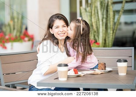 Cute Little Daughter Kissing Her Mother On The Cheek While At A Restaurant