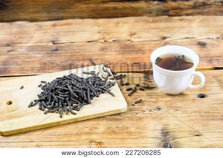 Close-up Fermented Ivan-tea On Wooden Board. Dry Herbal Natural Tea. White Cup With Ivan-tea