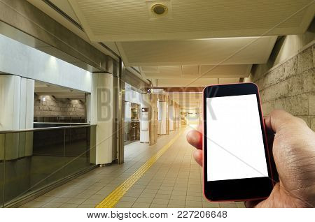 Hand Using Smart Phone Isolated Blank Screen With Blurred Image Of Subway At Railway Station, Lifest