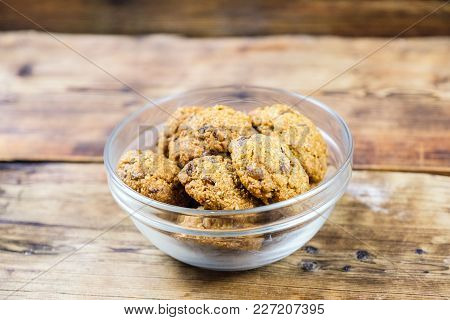 Homemade Oatmeal Cookies With Raisins In Glass Plate On Wooden Background. Side View