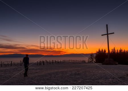 Hiker Walking To Summit Cross Of Mountain Schoeckl With Beautiful Sunset And Low Stratus Over The Va