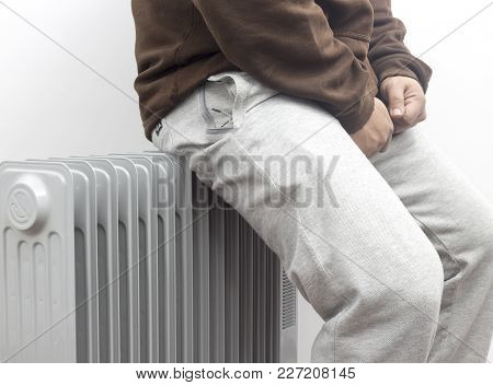 The Freezing Man Sitting And Heating His Ass On Oil Heater