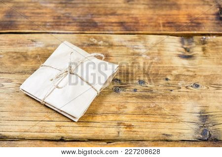 Gift Wrapped Kraft Paper On Wooden Background. Left On Photo