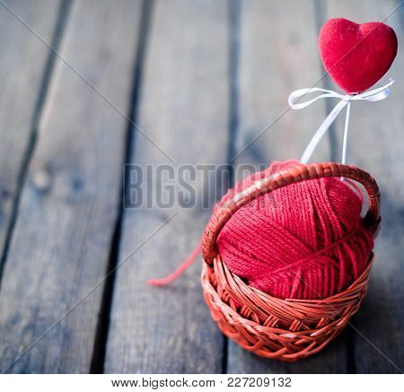 Wicker Basket On A Wooden Background With A Ball Of Threads And Hearts.