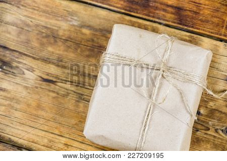 Close-up Gift Wrapped Kraft Paper On Wooden Background. Left On Photo
