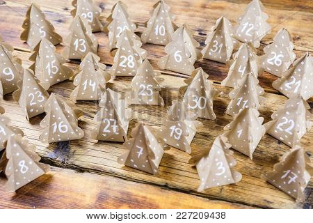 Handmade Christmas Advent Calendar Christmas Trees Kraft Paper With Numbers In Wood Background