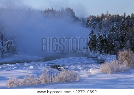Cold Morning Mist Above The Rapids. Snow And Forests Up North. Bushes.