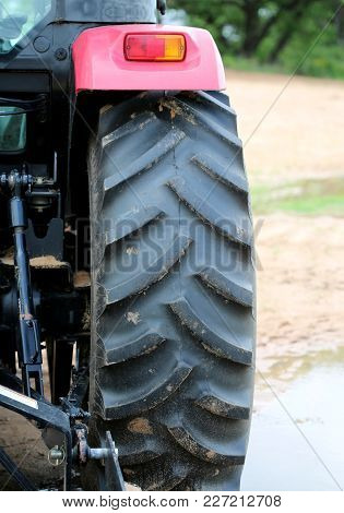 Red tractor parts: large modern tractor on the field, rear view.  The back wheel