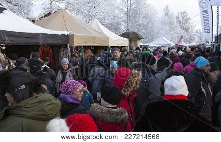 Jokkmokk, Sweden On February 03. View Of Well-dressed People Move Along The Market Stalls On Februar