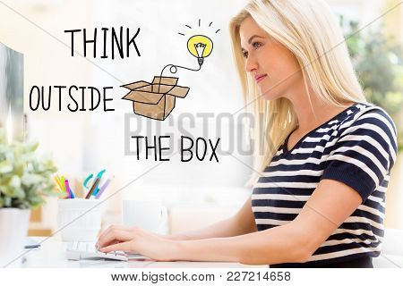 Think Outside The Box With Happy Young Woman Sitting At Her Desk In Front Of The Computer