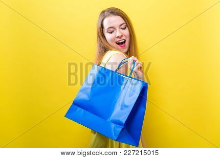 Young Woman Holding A Shopping Bag On A Yellow Background