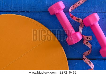 Dumbbells And Tape Measure On Wooden Background With Copy Space. Saturated Colors (blue, Orange, Pin