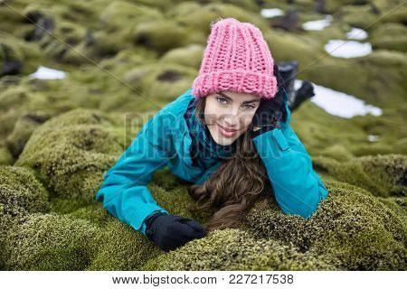 Smiling Girl Lies On The Green Moss Field With Remains Of Snow In Iceland. She Wears A Blue Jacket W