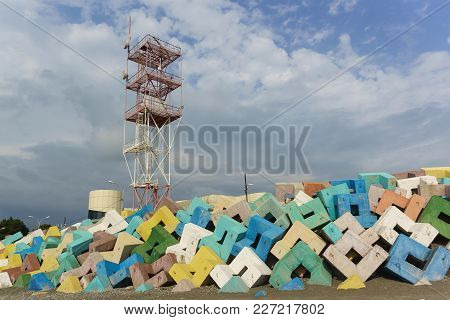 Navigation Tower Of Adler Sea Port Over Bright Concrete Protective Structures. Cloudy Day In Early S