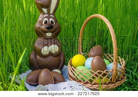 Egg hunt concept. Chocolate Easter bunny with chocolate eggs and sweets in Easter basket on green grass background. Chocolate Easter bunny on green grass background. Chocolate Easter bunny with Easter basket. Easter bunny chocolate egg hunt. Easter Bunny