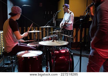 Band Of Young Musicians Performing In Dim Recording Studio Making New Album, Drum Set In Foreground