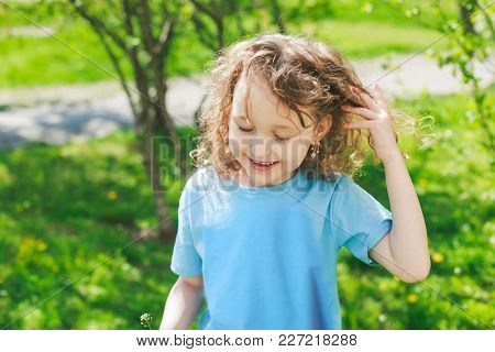The Girl Is Straightening Her Hair. The Girl Is Smiling. A Child On A Walk In The Spring Against The