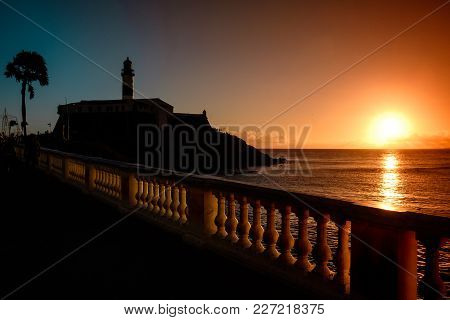 Nice Sunset With The Silhouette Of A Lighthouse And A Palm Tree. The Red, Warm Light Of The Sun Is R