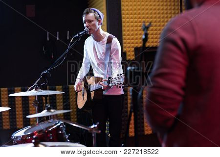 Portrait Of Young Musician Performing In Dim Recording Studio While Making New Album With His Band,
