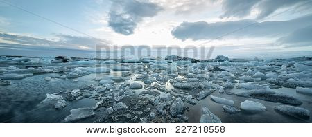Ocean Surface With Ice Floes On The Background Of The Snow Mountains And Cloudy Sky In Iceland. Sunl
