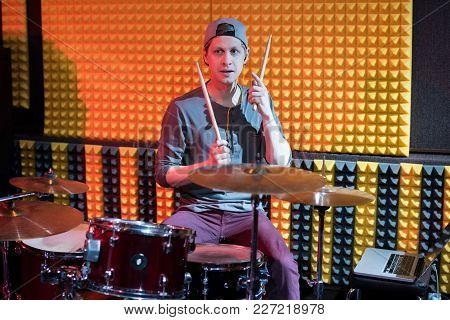 Portrait Of Young Man Playing Drums Performing In Dim Recording Studio While Making New Album With H