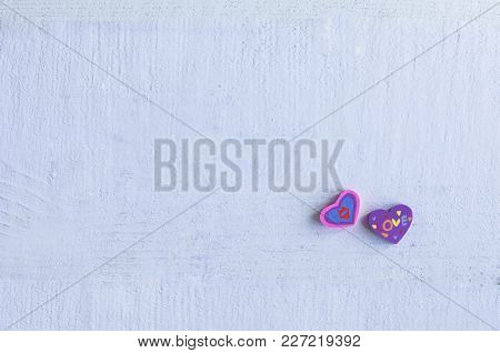 Two Erasers  In The Shape Of A Heart On Blue Background.