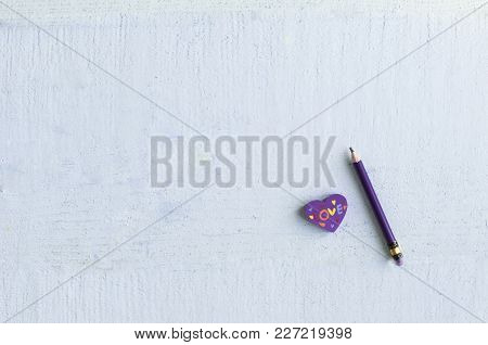 Purple Eraser In The Shape Of A Heart With A Pencil On A Blue Background