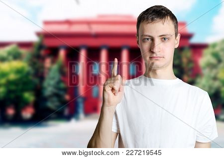 Serious Young Guy Showing Thumbs Up Against Background Of University. The Man Calls For Attention, C