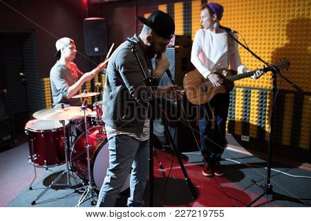 Band Of Young Musicians Performing In Dim Recording Studio Making New Album, Hip Hop Singer In Foreg
