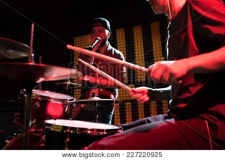 Portrait Of Hip-hop Singer Performing With His Band In Recording Studio, Drummer In Foreground Scene