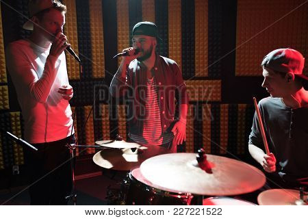 Portrait Of Modern Hip-hop Band Performing In Recording Studio Lit By Red Lights While Making New Al