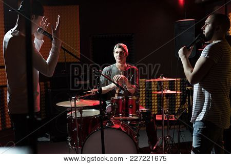 Portrait Of Modern Hip-hop Band Rehearsing In Recording Studio Lit By Dim Lights While Making New Al