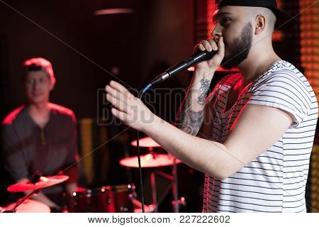 Side View Portrait Of Tattooed Hip-hop Singer With His Music Band Performing In Dim Recording Studio