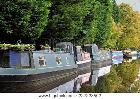 Line Of Traditional Narrow Boats And Houseboats Moored Along The Canal With Trees Reflected In The S